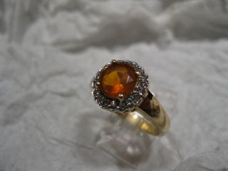 MEXICAN FIRE OPAL SET IN 14 KARAT GOLD WITH A RING OF WHITE DIAMONDS